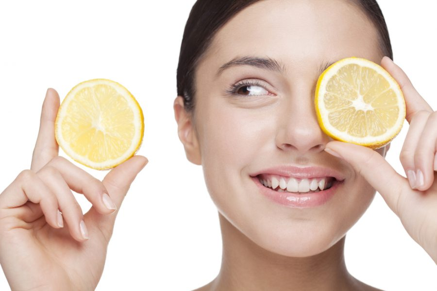 young woman holding lemon slices in front of eye