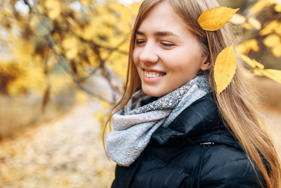 Portrait of a beautiful, sweet, cheerful girl who walks in the Park in autumn season